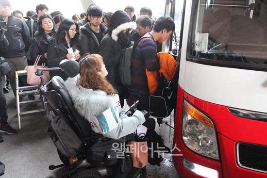 휠체어를 이용하는 장애인이 고속버스를 타기위해 줄서고 있는 사진