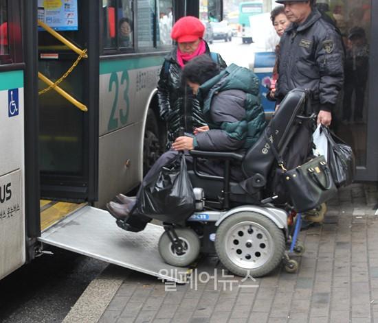 휠체어를 탄 한 장애인이 저상버스에 타고 있다.