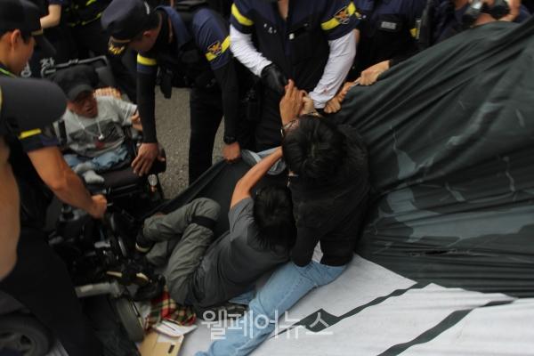 육교에서 걸린 현수막을 철거하려는 경찰과 현수막을 지키기 위한 활동가.